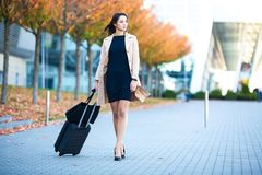 Vacation. Smiling female passenger proceeding to exit gate pulling suitcase through airport concourse.  royalty free stock image