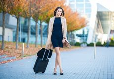 Vacation. Smiling female passenger proceeding to exit gate pulling suitcase through airport concourse.  royalty free stock photo