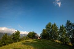 Vacation sulla cabina di legno circondata dagli alberi, chiaro cielo blu della montagna nell'estate immagini stock libere da diritti