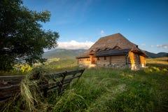 Vacation sulla cabina di legno circondata dagli alberi, chiaro cielo blu della montagna nell'estate fotografia stock libera da diritti