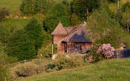 Vacation sulla cabina di legno circondata dagli alberi, chiaro cielo blu della montagna nell'estate fotografia stock