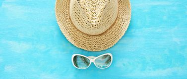 Vacation and summer banner with fedora beach hat and sunglasses over blue wooden background. Stock Photos