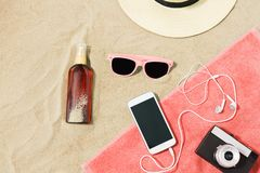 Smartphone, camera, towel, hat and shades on beach stock images