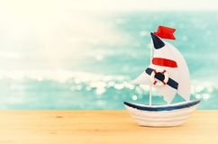 Vacation and summer image with boat over wooden table and sea landscape. Vacation and summer image with boat over wooden table and sea landscape Royalty Free Stock Images