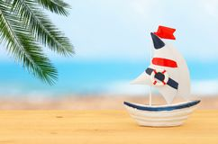 Vacation and summer image with boat over wooden table and sea landscape. Vacation and summer image with boat over wooden table and sea landscape Royalty Free Stock Photos