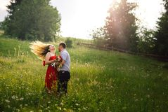 Vacation on the sunny meadow of the happy hugging couple in love. The charming young girl is shaking her long curly. Blonde hair Royalty Free Stock Image