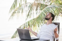 Vacation and technology. Work and travel. Young bearded man using laptop computer while sitting at beach cafe bar. royalty free stock photos
