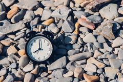 Vacation time. Alarm clock on the beach.  stock photo
