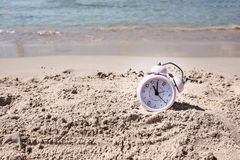 Vacation time. Alarm clock on the sand.  royalty free stock photos