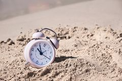 Vacation time. Alarm clock on the sand.  royalty free stock image