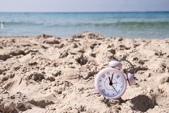 Vacation time. Alarm clock on the sand.  royalty free stock photography