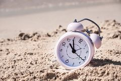 Vacation time. Alarm clock on the sand.  royalty free stock photo