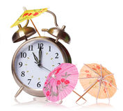 Vacation time concept. Alarm clock and cocktails umbrellas isolated Stock Photos