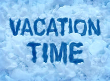 Vacation Time. Concept with a cold freezing snow background with text embossed in the ice crystals as a symbol for escaping the frigid winter weather to a Royalty Free Stock Photography