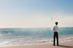 Vacation time finally. Mixed media. Businessman standing on ocean coast and enjoying the view. Mixed media Stock Photography