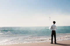 Vacation time finally. Mixed media. Businessman standing on ocean coast and enjoying the view. Mixed media Royalty Free Stock Image