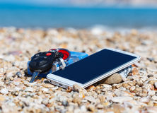 Vacation time, smart phone, car keys and cigarettes, on the seashells in the beach Stock Photography
