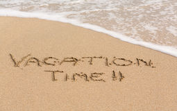 Vacation Time written in sand with sea surf Stock Images