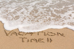 Vacation Time written in sand with sea surf Stock Photo