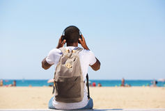 Vacation time. Young man sitting by beach with bag listening to music on headphones Royalty Free Stock Image