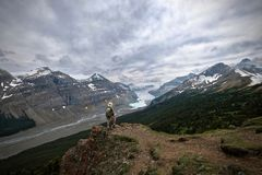 Brave man hiker on mountain top looking at view of Columbia Icefied glacier and moraine lake. Vacation travel in Canadian Rockies. Columbia Icefield. Banff stock photography