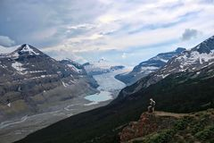 Brave man hiker on mountain top looking at view of Columbia Icefied glacier and moraine lake. Vacation travel in Canadian Rockies. Thunderstorm over Columbia stock images