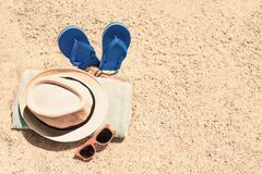 Vacation and travel concept. Beach, sand and sea with towel, fli. P flops and summer accessories with copy space Royalty Free Stock Image