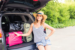 Vacation, Travel concept - young woman ready for the journey on summer holidays with suitcases and car Stock Photography