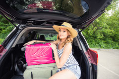 Vacation, Travel concept - young woman ready for the journey on summer holidays with suitcases and car Stock Image