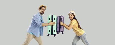 Funny tourist couple having fun touching with luggage suitcase studio shot. Vacation and travel. Funny overjoyed tourist couple or friends having fun touching