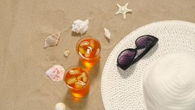 Cocktails, sun hat and sunglasses on beach sand. Vacation, travel and summer concept - two glasses of aperitif cocktails, sun hat, sunglasses and seashells on stock video footage