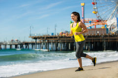 Vacation travel woman cardio exercise on beach jogging fit thin slim body by pier Stock Image