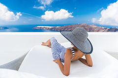 Vacation travel woman relaxing enjoying Santorini. Looking at famous view of Caldera. Young lady lying down on sun bed sofa lounge chair on holidays. Amazing stock photography