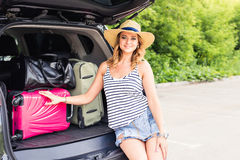 Vacation, Travel - young woman ready for the traveling. suitcases and car. Vacation, Travel - family ready for the travel for summer vacation. suitcases and car Royalty Free Stock Images