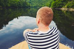 Vacation trip on the river. Handsome man is sitting on the prow of the boat Stock Photos