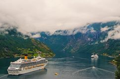 Vacation, trip, wanderlust. Cruise ship in norwegian fjord. Passenger liner docked in port. Travel destination, tourism. Geiranger, Norway - January 25, 2010 stock photography