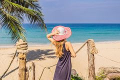 Vacation on tropical island. Woman in hat enjoying sea view from wooden bridge.  stock images