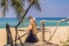 Vacation on tropical island. Woman in hat enjoying sea view from wooden bridge.  royalty free stock images
