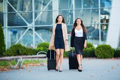 Vacation. Two happy girls traveling abroad together, carrying suitcase luggage in airport.  stock images