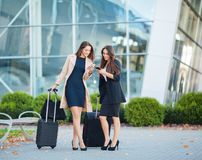 Vacation. Two happy girls traveling abroad together, carrying suitcase luggage in airport.  stock image