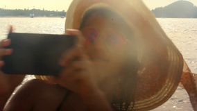 Vacation woman in hat with uses phone at the beach stock video