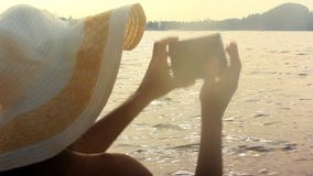 Vacation woman in hat with uses phone at the beach stock footage