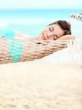 Vacation woman relaxing on beach. In hammock on summer holidays resort. Beautiful happy multiracial Asian Chinese / Caucasian young woman Royalty Free Stock Images