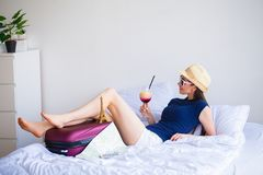 Vacation. Woman Who is Preparing for Rest. Young Beautiful Girl Sits on the Bed. Portrait of a Smiling Woman. Happy Girl royalty free stock images