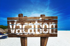 Vacation wooden sign with a beach on background Stock Photos