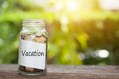 Vacation word with coin in glass jar on wooden table. Royalty Free Stock Photo