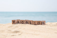 Vacation word on sunny beach with ocean background Stock Images