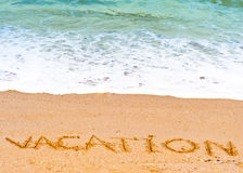 Vacation word written in the sand on the beach blue waves in the background. 