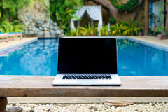 Vacation work with laptop on bench at pool Stock Image