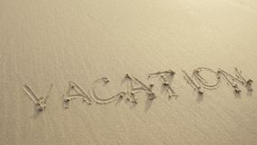 VACATION written on the beach sand washed aways by waves. Stock Photos